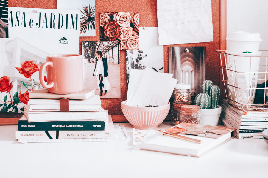 Cute desk with books and pink coffee cup