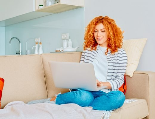 A woman working on her laptop on a couch